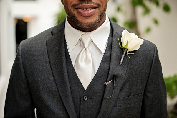 African American groom in three-piece suit and flower on lapel