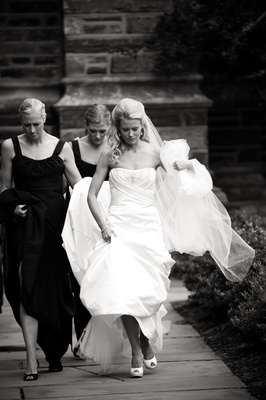 black and white bridesmaids help carry the bride's train