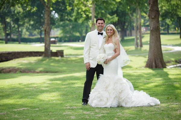 Bride in Vera Wang ruffle mermaid wedding dress and groom on lawn