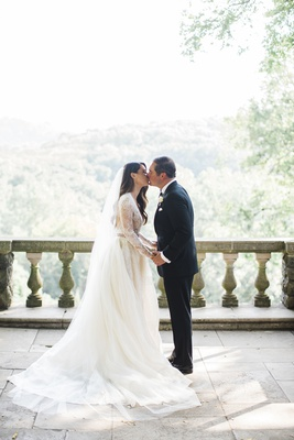 bride in monique lhuillier lace long sleeve a-line gown, cathedral veil, kisses groom on balcony