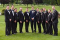 groomsmen in black suits with navy bow ties and groom in navy suit with black bow tie