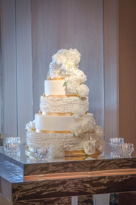 five-tier wedding cake with ruffled tiers, white peonies, gold ribbon