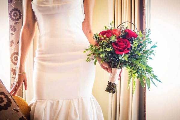 a bride holding a bouquet of red roses and leafy greenery