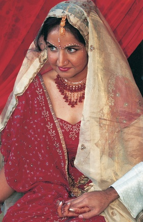 Bride in red dress with gold veil and jewelry