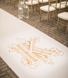 wedding ceremony gold chiavari chairs floating candles white aisle runner gold monogram