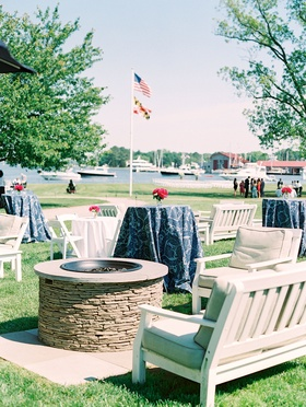 Seating area and fire pit on lawn at venue river view blue navy linens pink flowers lounge furniture