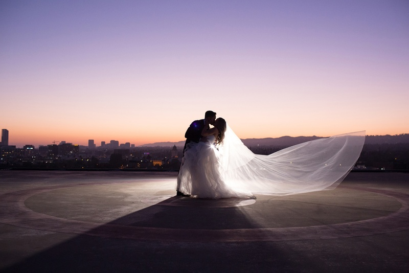 groom dips bride, veil blowing in wind, rooftop picture of newlyweds at sunset
