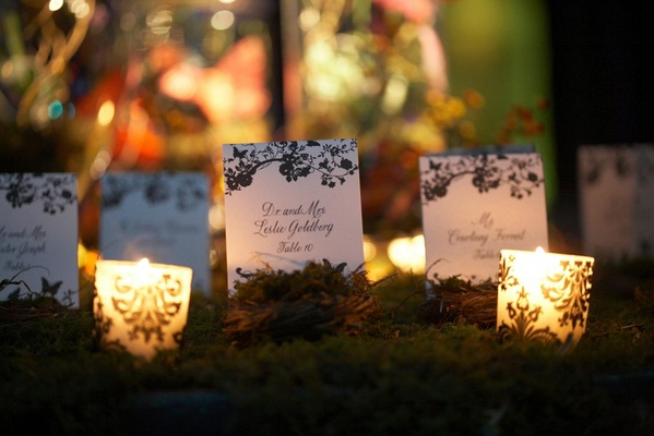 place cards in bed of moss surrounded by candles
