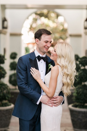 bride in sleeveless wedding dress ivory with groom in navy suit smiling laughing long blonde hair