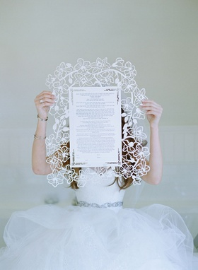 Bride in voluminous white Vera Wang ball gown holding lasercut chuppah with flower motif