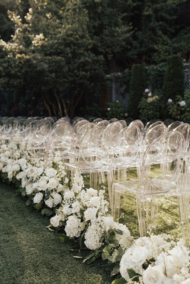 outdoor wedding ceremony on grass lawn guest chairs ghost clear white rose hydrangea stock greenery