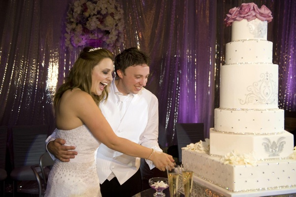 Bride and groom cut white cake with rhinestones