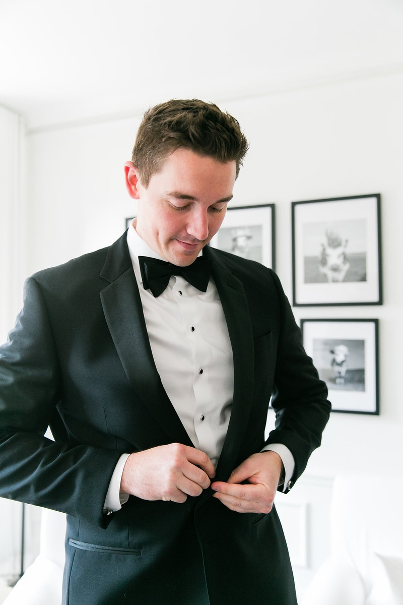 Groom in groom's suite black and white tuxedo buttoning up before wedding