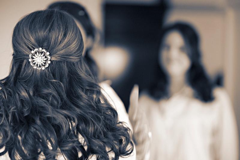 Black and white photo of bride's hairdo with a round rhinestone barrette