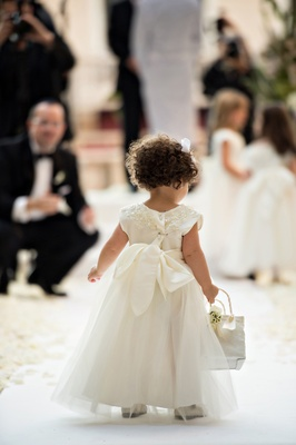 curly-haired flower girl with basket walks up the aisle