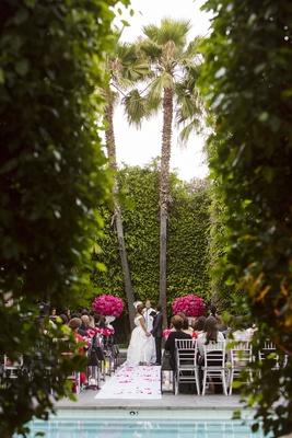 Bride and groom in between palm trees at hotel pool wedding