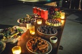 a delicious dessert table with small votive candles including mexican cookies and candies