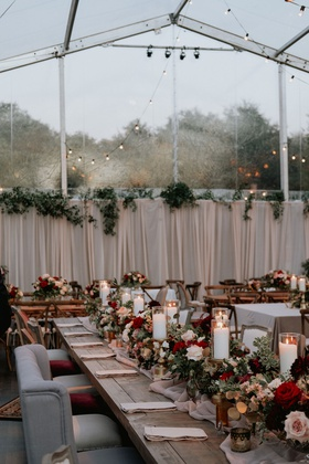 wedding reception tent clear string lights settee wood table low centerpiece candles burgundy flower