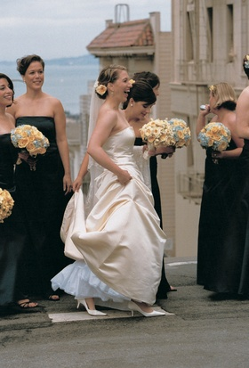 bridesmaids wear black dresses and carry bouquets on san francisco street