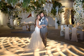 bride in form fitting wedding dress groom in grey tuxedo dance floor with woven light projection