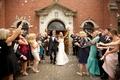 Wedding guests toss petals at church wedding couple