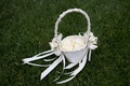 White flower girl basket with ivory rose petals and white ribbon