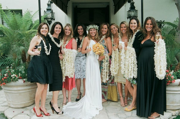 Bride with female friends passing out white orchid leis
