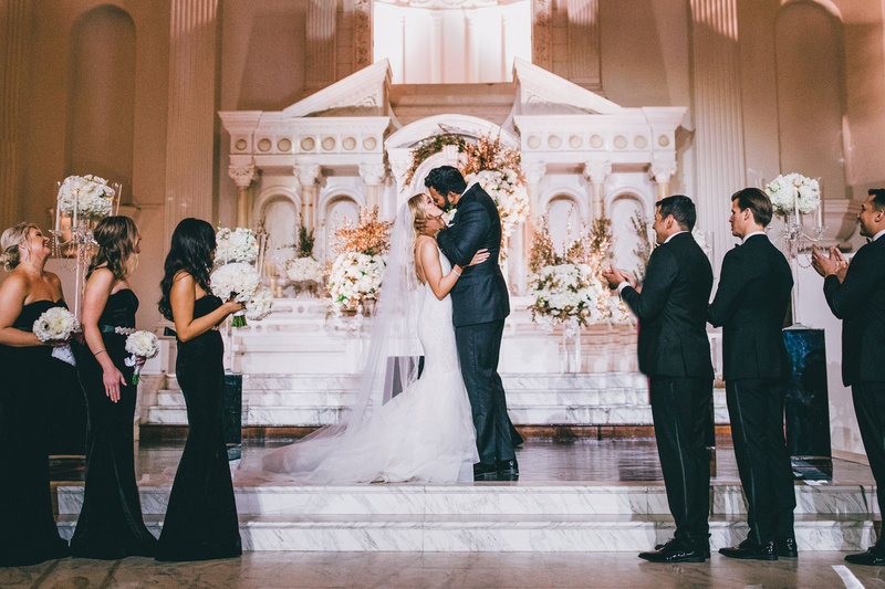 bride and groom kiss on marble steps altar wedding ceremony vibiana venue bridesmaids in black