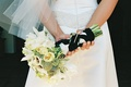 Bride holds white flower bouquet behind her back