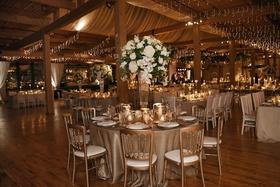 wedding reception wood beams drapery greenery white centerpieces twinkle lights star sky design