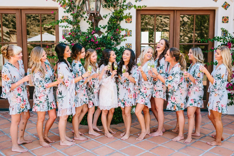 bride with white lace robe and bridesmaids in ruffle light blue flower print robe champagne spanish