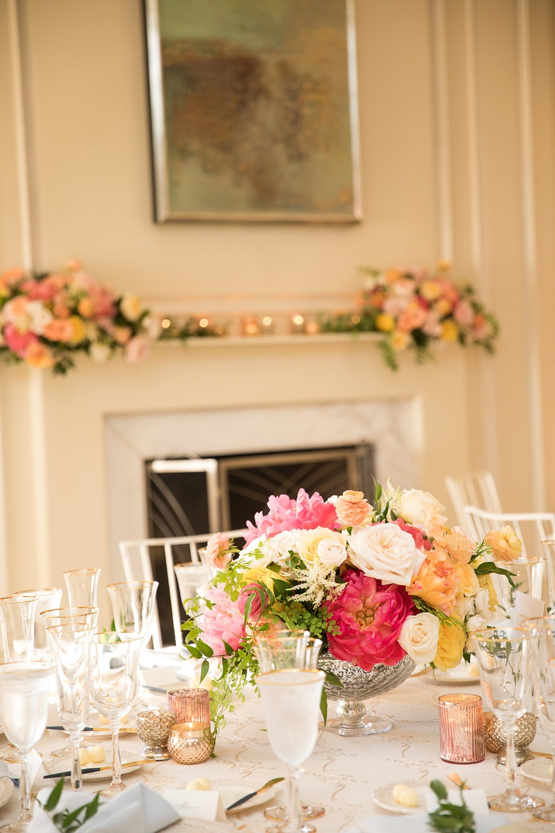 wedding reception table low centerpiece footed vase with pink white yellow orange flowers candles