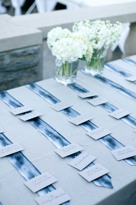 wedding escort cards pinned to blue silk ties on table with grey linen and white flowers