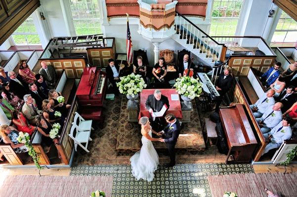 Bride in a Berta Bridal gown exchanges vow with groom in a navy Ralph Lauren tuxedo