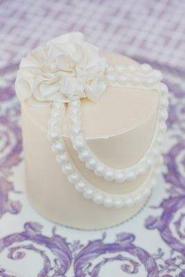 Personal white wedding cake with sugar flower and string of pearls on Versace plate