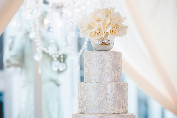 Silver wedding cake with round tiers, white icing, and mercury glass vase
