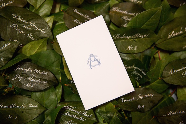Ceremony program with blue monogram on green leaves