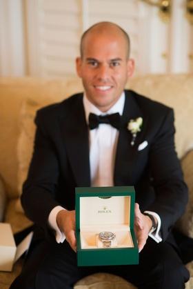 Groom in tuxedo holding Rolex watch in green box platinum