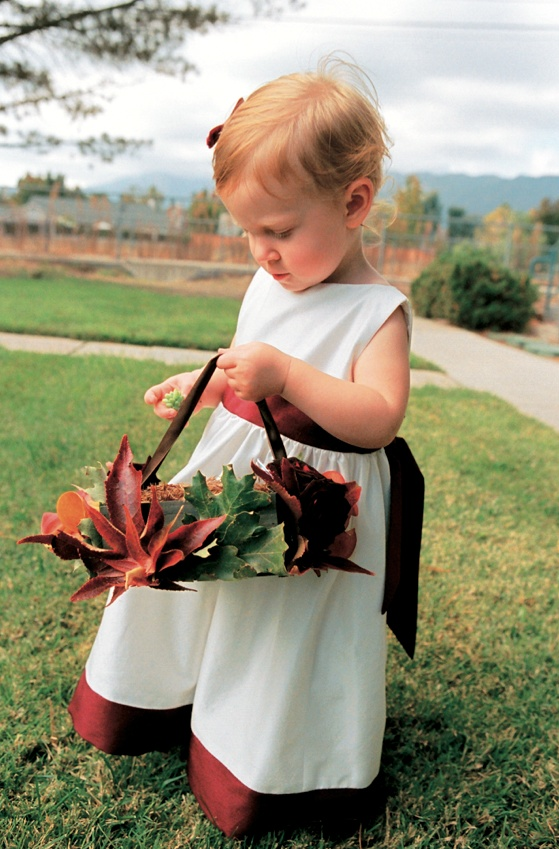 flower girl in white dress with red trim carries basket lined with leaves