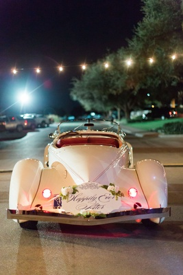 Happily ever after with white flowers greenery classic convertible getaway car just married wedding