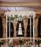 square wedding cake on lucite table, calla lilies suspended above