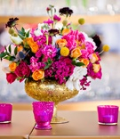 Flower arrangement with pink and orange roses in gold glitter vase