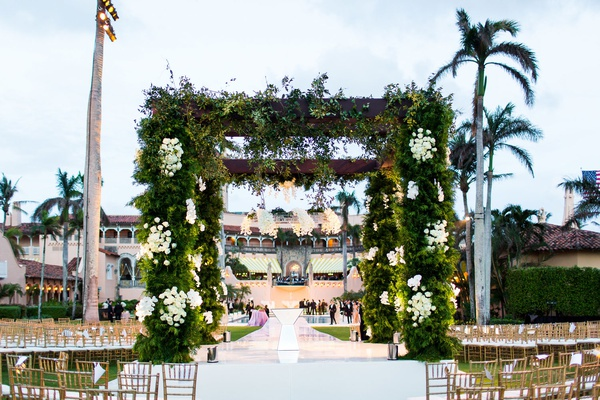outdoor wedding ceremony structure wood arbor greenery white rose flowers in the round seating