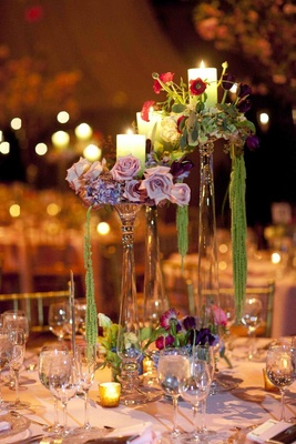 Wedding reception centerpieces of crystal candle holders with candle, purple, green, and red flowers