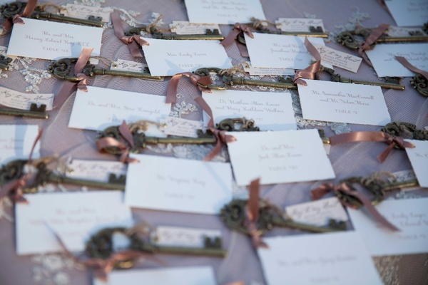 white escort cards with golden keys adorned with soft pink ribbons
