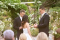 bride and groom exchange rings in front of greenery arbor