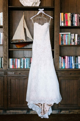 Alencon lace wedding dress with sweetheart neckline, sweep train on hanger in library