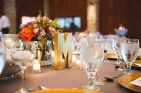 gold letter m and flower bouquet on table