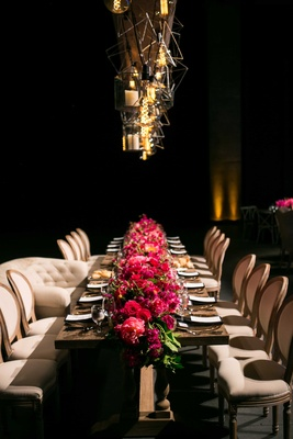 long wooden head table bright pink floral runner geometric lighting concept dark reception space
