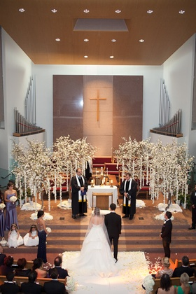 Bride and groom standing at altar of Armenian church for wedding ceremony with trees